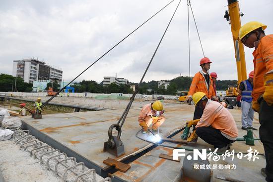 工人在进行站东路延伸段工程钢箱梁吊装焊接。