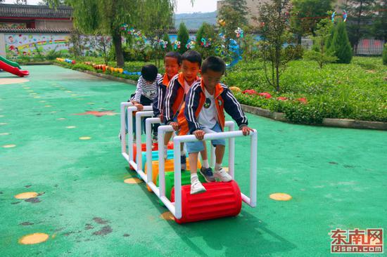孩子们几人合作玩着踩滚筒的游戏。(东南网记者 刘玮 摄)