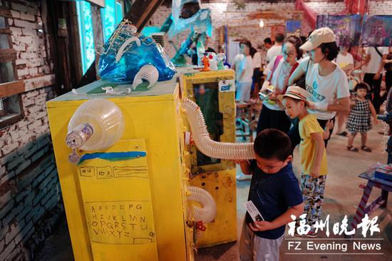 """家长带着孩在""""垃圾美术馆""""参观。"""