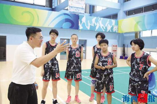 林荣芊(左一)与篮球队员们交流训练心得。