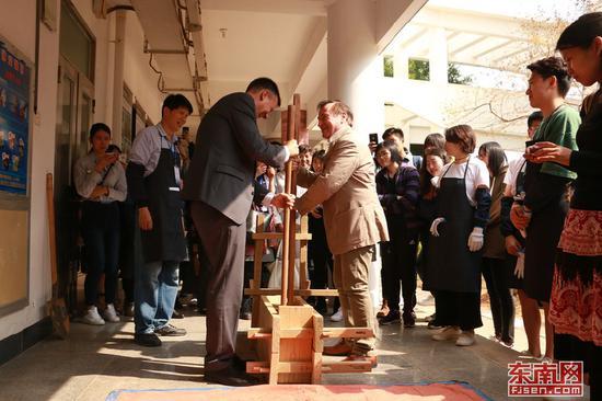 去年,在厦大嘉庚学院举办的闽南传统建造技艺研讨会中,来宾体验土楼夯土。刘可鑫 摄