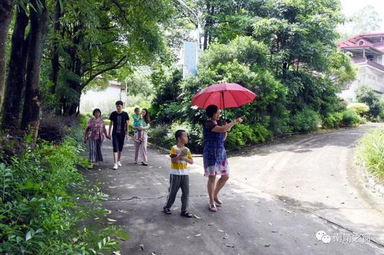 """▲张丽洪一家人在""""小公园""""似的村道上散步。陈巧云 摄"""