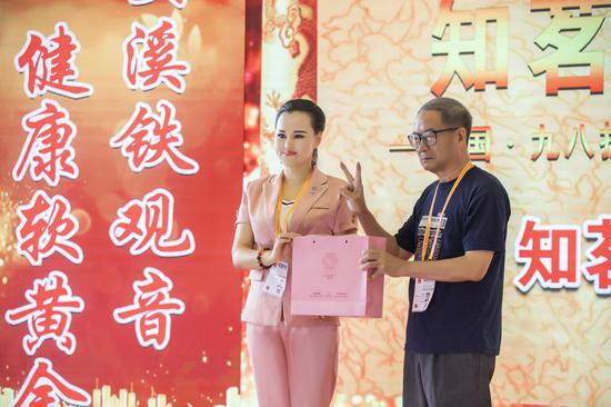 知茗直播基地负责人刘敏珍向厦门大学知名教授郑启五老师赠送东方茗珠茶品