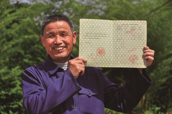 武平县农林李桂林展示他拿到的全国第一本林权证