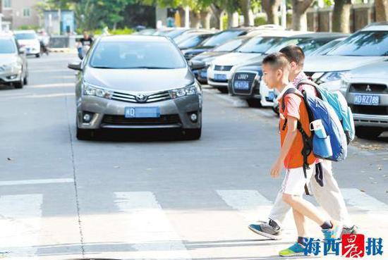 昨日傍晚,金尚小学附近路口,车辆礼让学生。记者 唐光峰 摄