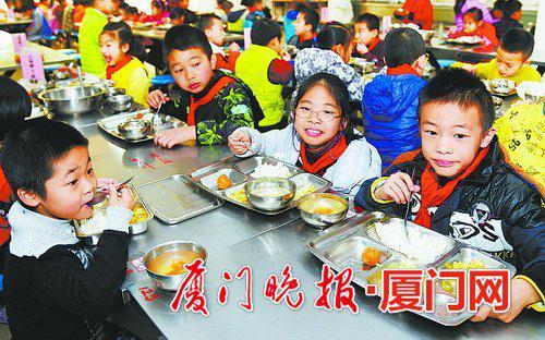 江头中心小学校长经常陪餐,学生在食堂开心用餐。  刘东华 摄