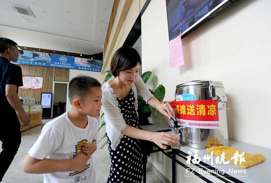 9日上午,在博方堂门诊部金山分店,市民在装凉茶给小孩喝。