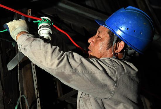 7月11日晚,福州供电公司抢修人员正在修复因台风受损的接户线(陈蒸摄)