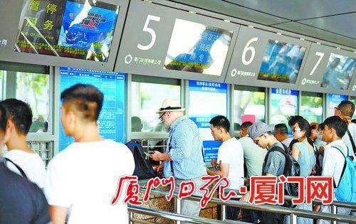 国外游客在轮渡码头购票准备前往鼓浪屿游览。(本报记者 林铭鸿 摄)