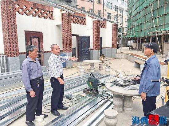 张智厚(中)和自管小组成员讨论小区改造。记者 晋君 摄