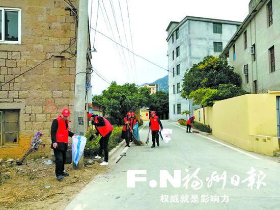 江田镇党员志愿者清理路边垃圾。
