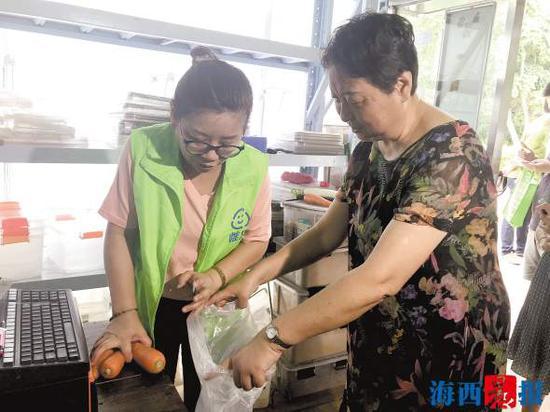在瑞景公园小区,居民拿厨余垃圾兑换蔬菜。 记者 钟宝坤 摄