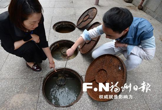 工作人员检查隔油池残渣与油污清掏情况。