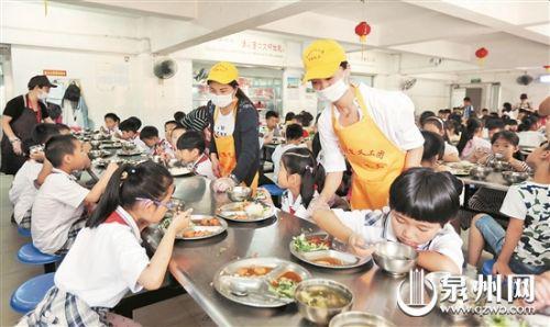 帮厨义工督促孩子们好好吃饭