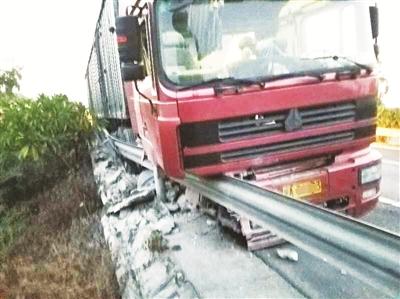 司机疲劳驾驶半挂车冲撞护栏后卡路缘 所幸无人受伤