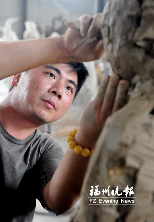 林成杰正在创作泥塑。