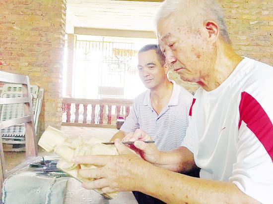 纪万水(右一)和儿子沉迷在手工木雕的乐趣中。记者 陈雅玲 摄