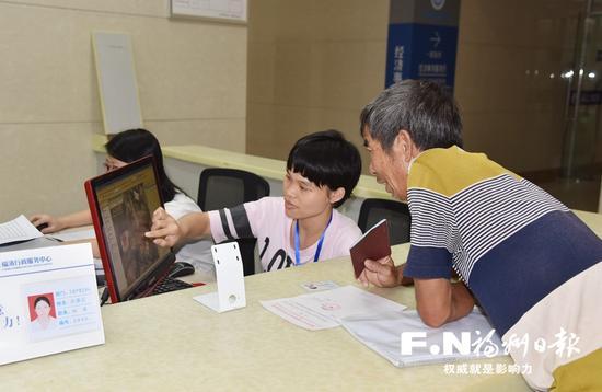 福清行政服务中心不动产登记服务厅内,工作人员正为市民办理权籍调查。(市国土局提供)