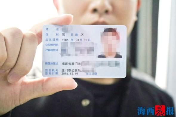 申请人展示已到手的居住证。记者 陈小斌 摄