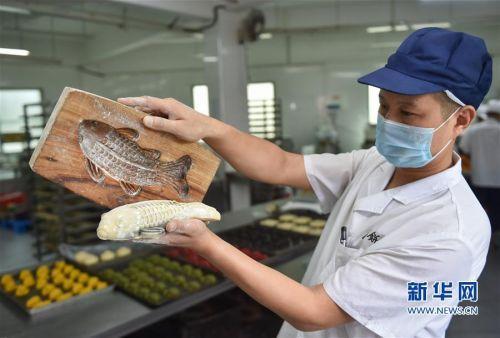 """9月29日,福州老字号""""百饼园""""的师傅用传统手工木制模具制作""""鲤鱼饼""""。"""