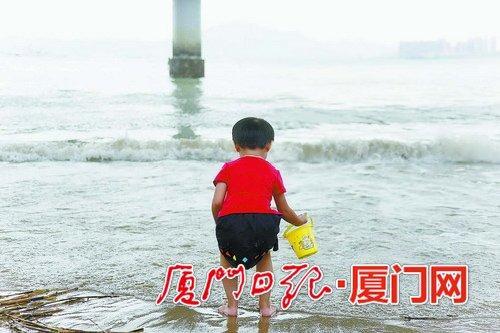 昨日多云升温。图为在海边玩耍的孩童。(本报记者 姚凡摄)