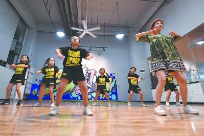 创业者房琰琰(右)在自己创办的街舞培训学校里,向小学生教授街舞。