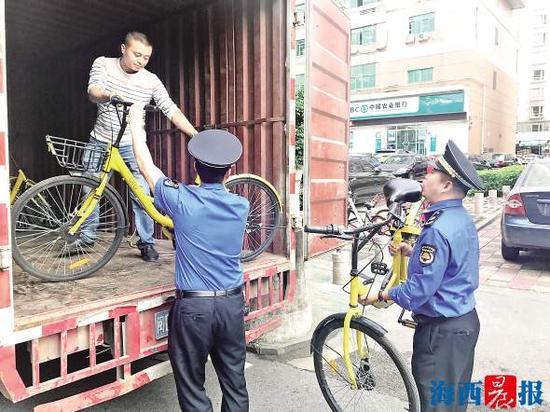 城管执法人员将乱停放的共享单车搬上厢式货车。