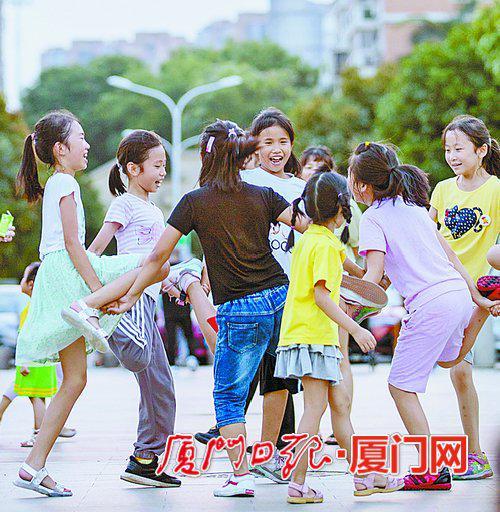 昨日天气依旧闷热,图为傍晚孩子们在一起玩耍。(记者 张奇辉 摄)