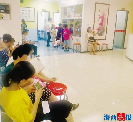在培训机构等候孩子下课的家长们。 记者 许蔚菡 摄