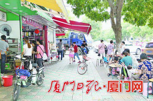 餐饮店跨店经营,在店面外支起了餐桌。(记者薄洁摄)