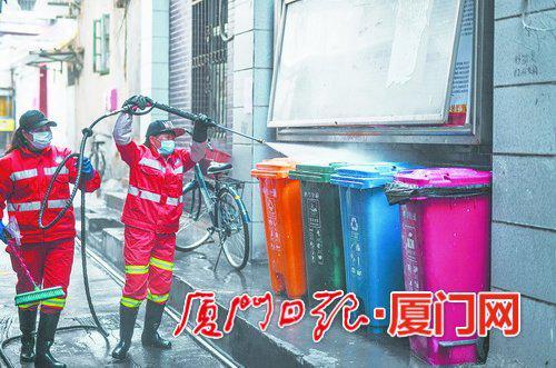 环卫工使用水枪冲洗小巷中的角落。