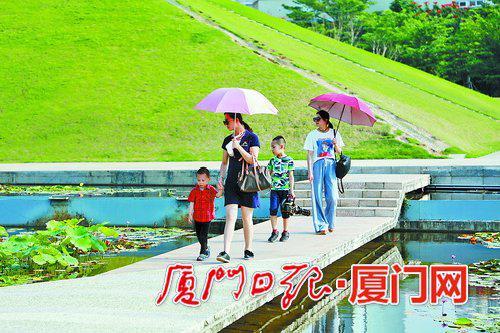 由于阳光炙热,不少市民外出时打伞。(本报记者 王协云 摄)
