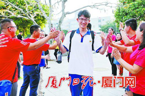 科技中学考生与老师和同学击掌。(本报记者 王协云 摄)