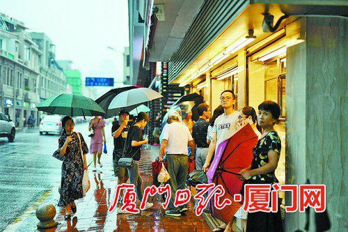 不少行人站在人行道观望雨势。(本报记者 林铭鸿 摄)