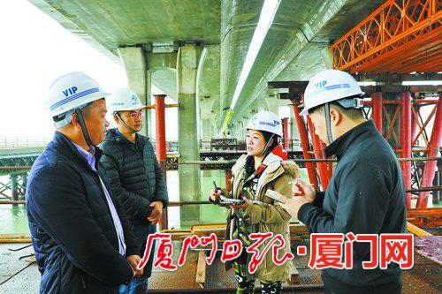 记者在施工现场采访建设者。