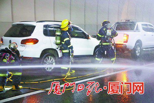 消防队员架设水枪灭火,并破拆小车救人。