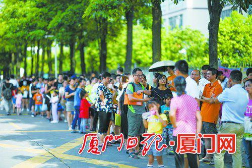 小学校园外排队等候报名的家长和学生队伍。(本报记者 林铭鸿 摄)