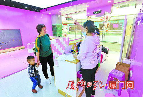 位于加州商业广场的一家玩具租赁馆内,家长在咨询如何租玩具。