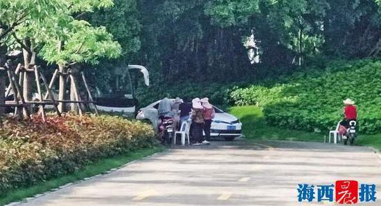"""停车场的""""管理员""""正在向进入车辆收费。"""