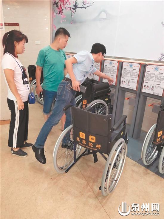 工作人员指导市民如何扫码租借共享轮椅