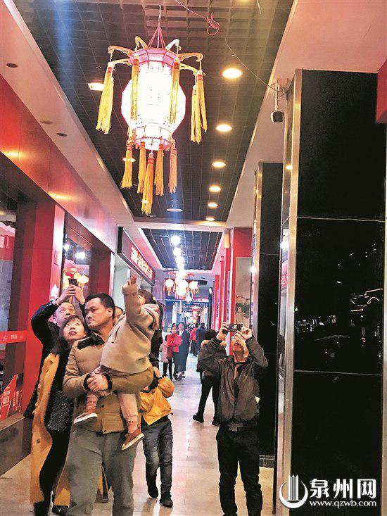 陈华的朋友一家子在新门街赏花灯,感受泉州元宵盛况。(王金植 摄)