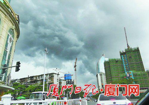 昨日时有阵雨,市区上空乌云滚滚。(本报记者姚 凡摄)