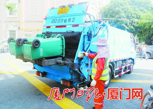 环卫工人将厨余垃圾倒入收运车内。
