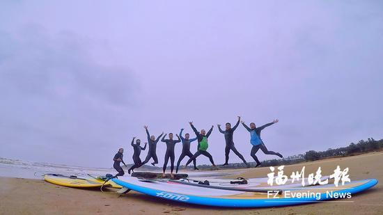 8名冲浪好手开心跃起,合影留念。