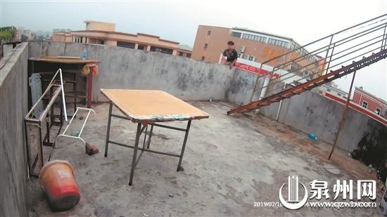 男子坐民房楼顶的围栏上欲轻生(视频截图)