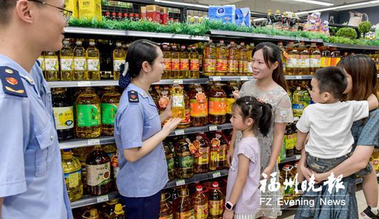 工作人员在超市现场指导市民如何选购安全食品。