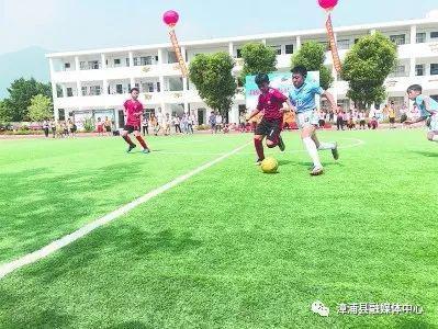 南浦中心学校的学生在足球场上踢球。↑