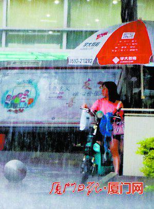 昨日岛内突降暴雨,一位行人躲在路边的大伞下。(本报记者 何炳进 摄)
