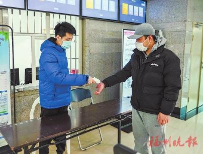 省体育中心内,工作人员为市民测量体温。