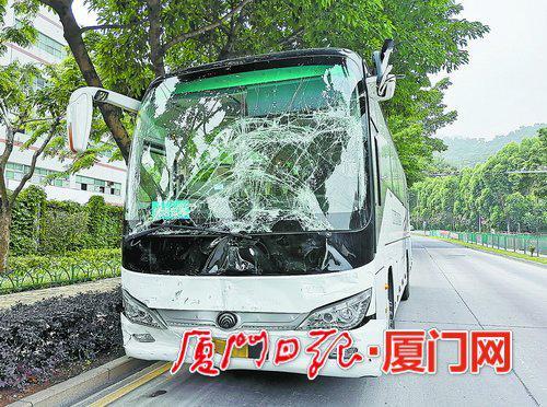 事故现场处置完毕,受损严重的大客车停在路边。